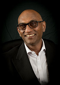 brown man with black glasses and a black suit smiling at the camera