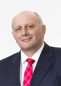 white man with sliver hair and a red tie smiling at the camera