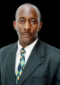 black man wearing a black suit and multi coloured tie looking at the camera